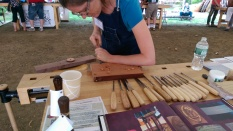 Mary May demonstrates her carving.
